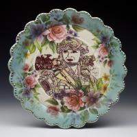Ornate blue and floral ceramic plate with image of female military person standing proud.