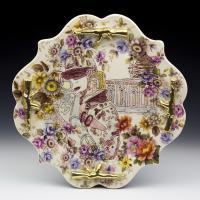 Ornate ceramic plate with image of female military person pointing gun at viewer.
