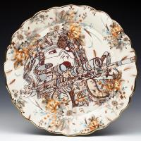 Ornate ceramic platter with image of female military person pointing gun to the right.