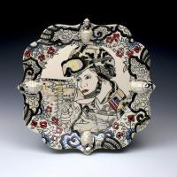 Ornate ceramic plate with image of female military person pointing gun at toward the left of viewer.