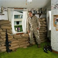 Jeff Gramlich in green carpeted bedroom with machine gun, sandbags, empty beer bottles, looking out at lawn.