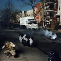 Jose Adames crouching on sidewalk in urban city, with explosion in street, trash on curb, and garbage truck in distance.