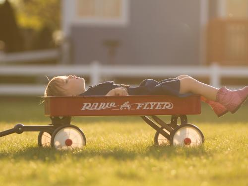 Horizontal photo of a child in a red wagon.