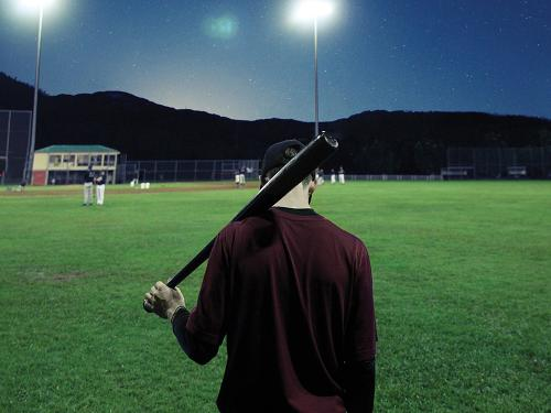 A man on an empty baseball field at night with lights on holds baseball bat over his shoulder.