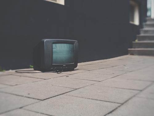 Horizontal close up of a black tv sitting on the ground.