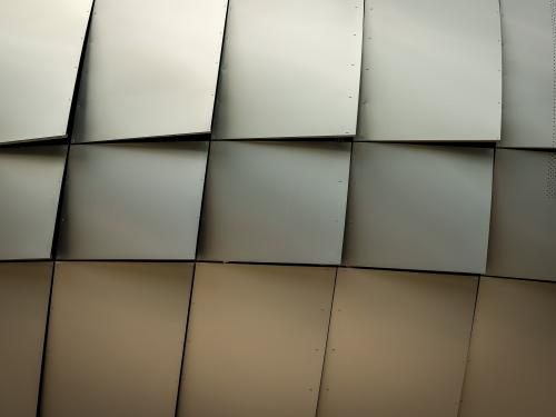 Horizontal close up of metal plates attached to a building.