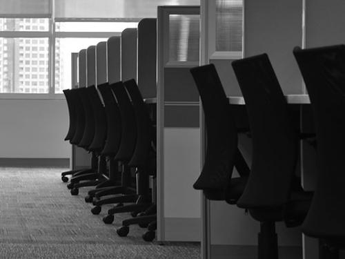 A black and white photo of a row of cubicles.