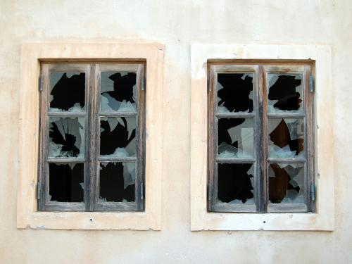 Horizontal photo of two symmetrical pane windows with the glass broken out.