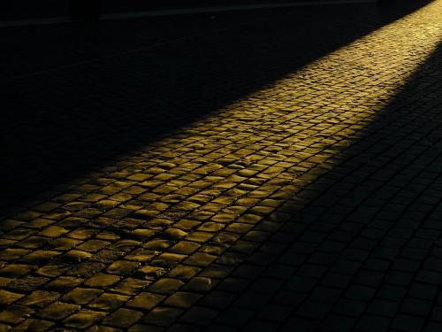 Cobblestones at night with beam of light running across them.