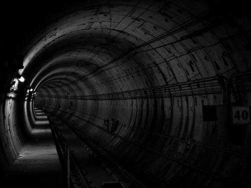 Horizontal photo of a black and white industrial tunnel.