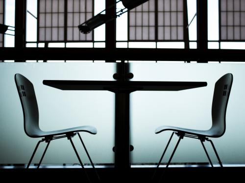 Horizontal photo of two chairs symmetrically facing a table.